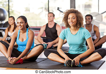Multi-ethnic group stretching in a gym before their exercise...