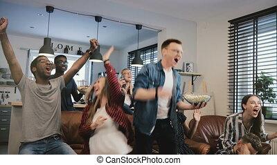 Multi-ethnic happy sports fans celebrate goal. 4K slow...