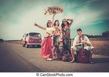 Multi-ethnic hippie hitchhikers with guitar and luggage on a...