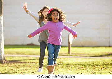 Multi ethnic kid girls playing running in park