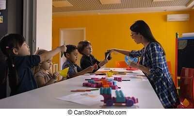 Multi ethnic kids creating origami at craft lesson - Group...