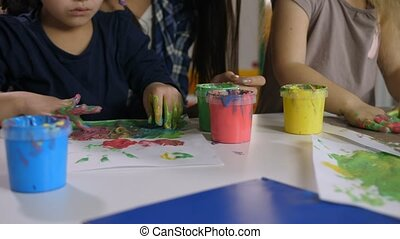 Multi ethnic little girls finger painting at class