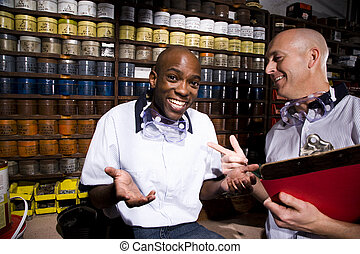Multi-ethnic male coworkers by shelves of colored inks in print shop