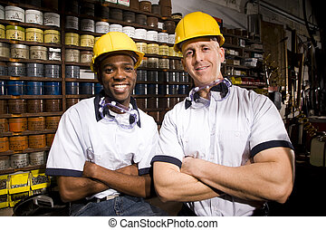 Multi-ethnic male coworkers by shelves of colored inks in ...
