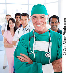 Multi-ethnic medical group smiling at the camera in a...