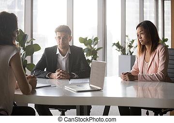 Multi-ethnic millennial business people negotiating in boardroom