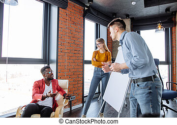 Multi-ethnic people planning business strategy with scheme on flip chart
