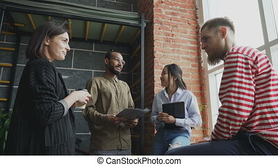 Multi-ethnic startup team is brainstorming and discussing new ideas in the modern office while standing near window