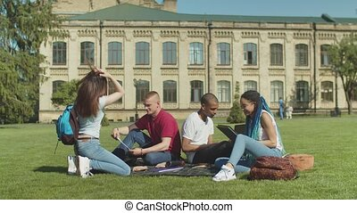 Multi ethnic students giving high five meeting on lawn