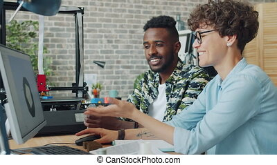 Multi-ethnic team making 3d printer models using computer and equipment in office, people are talking enjoying work. Innovation and business concept.