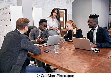 Multi-ethnic team of businesspeople meeting in modern office