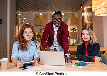 Multi-ethnic team of three young successful office managers in casualwear