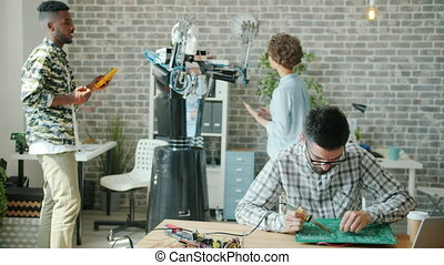 Multi-ethnic team of engineers is working in office with robot testing droid soldering circuit board with solderer. Robotics, engineering and modern technology concept.
