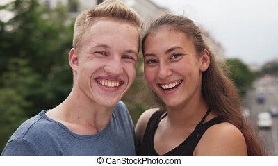 Multi-ethnic teenage couple having fun laughing in city