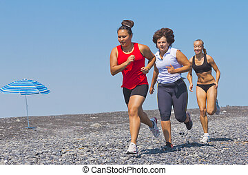 multi-ethnic women running sea beach