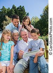 multi, generación, familia , con, un, computadora personal tableta, sentado, en el estacionamiento