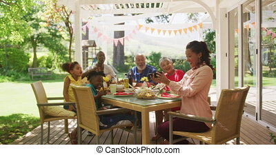 Multi-generation African American family spending time in garden together, sitting at a dinner table, using a smartphone and laughing, in slow motion.