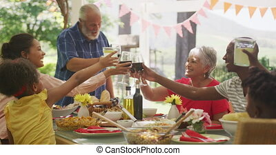 Multi-generation African American family spending time in garden together, sitting at a dinner table, making a toast, in slow motion.