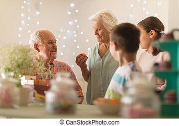 Multi-generation family celebrating birthday at home