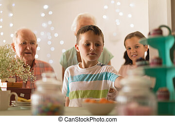 Multi-generation family celebrating birthday of grandson at home