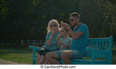 Multi generation family eating ice creams on bench -...