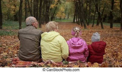Multi-generation family embracing in autumn park - Back view...