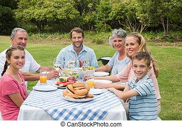 Multi generation family having dinner outside at picnic table