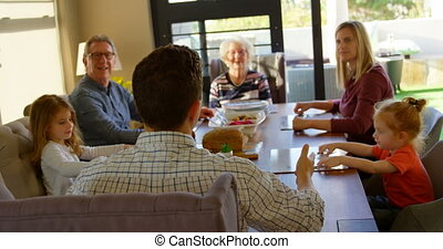 Multi-generation family interacting with each other on dining table 4k