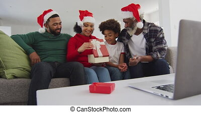 Multi-generation family opening gift box while having video chat on his laptop