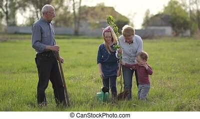 Multi generation family planting tree outdoor.
