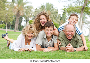 Multi-generation family relaxing in park