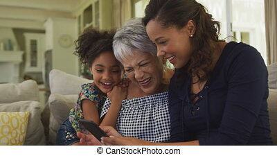 Senior African American woman, her adult daughter and her young granddaughter spending time at home together, sitting on a sofa in the living room, using a smartphone and smiling, in slow motion.