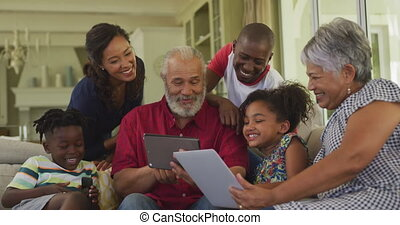 Six members of a multi-generation Caucasian family spending time at home together, sitting on a sofa in the living room, using tablets and smartphones, in slow motion.
