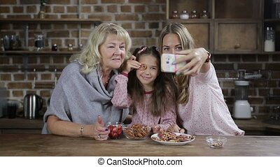 Multi generation family taking pictures in kitchen - Smiling...