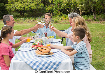 Multi generation family toasting each other at dinner outside