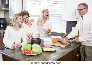 Multi-generational family making lunch in kitchen, laughing...