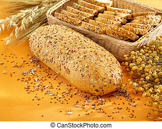 Freshly baked multi-grain bread and wheat on table
