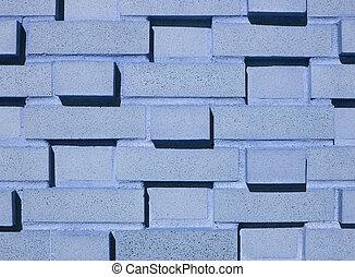 A pastel blue multi-layered and multi-sized brick wall.