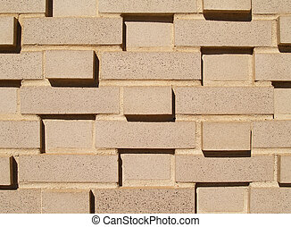 A light colored, beige multi-layered and multi-sized brick wall.