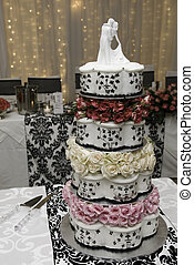 Multi layered wedding cake with bridal figurines and fairy lights