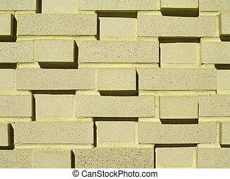 A pastel yellow multi-layered and multi-sized brick wall.