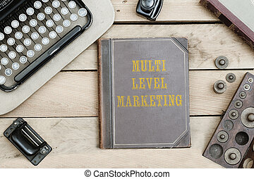 Multi Level Marketing on old book cover at office desk with...