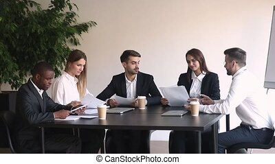 Different ethnicity partners millennial businesspeople gather at modern boardroom discuss new project analyzing report listens team leader negotiating planning future work, teamwork brainstorm concept