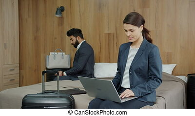 Multi-racial couple Arab man and Caucasian woman are using laptop and smartphone in hotel room, people are smiling enjoying devices. Technology and tourism concept.
