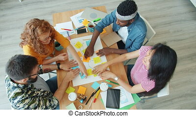 Multi-racial group of young cheerful people making collage in office working at project enjoying teamwork at desk. Creativity, business and cooperation concept.