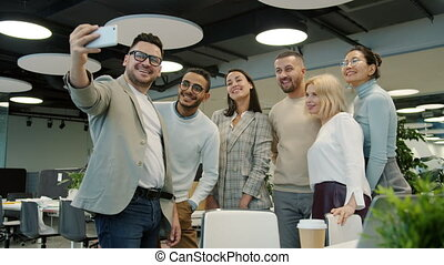 Multi-racial group of coworkers taking selfie in office room using smartphone posing smiling for mobile camera. People and self-portrait concept.