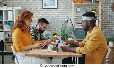 Multi-racial group of office workers men and woman are working with papers talking sitting at desk together. Teamwork, people and communication concept.