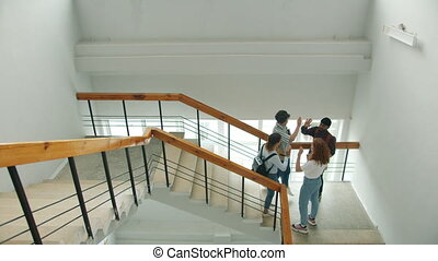 Multi-racial group of people students is meeting on stairs in college doing high-five talking smiling laughing. Casual life, campus and happy youth concept.