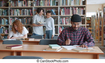 Multi-racial group of students studying in library with books reading talking