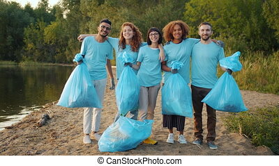 Multi-racial group of volunteers with trash bags hugging smiling on cleaned lake beach, girls and guys are enjoying charity work caring for environment.